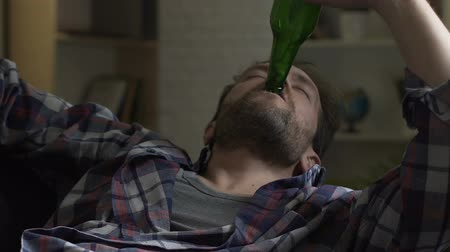 pitiable : Guy drinking beer from bottle and falling asleep sofa, alcoholism and bad habits.