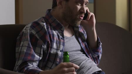 rendetlenség : Drunk tyrant sitting on sofa and talking on phone. Stock mozgókép