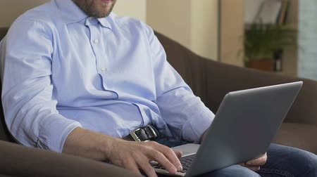 poeta : Male sitting on couch and typing e-mail on laptop computer.