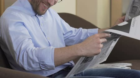 tényleges : Man in eyeglasses reading newspaper and smiling.