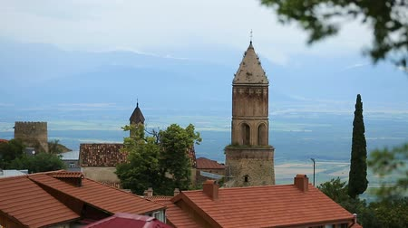 st stephen : Church building of St. George in Signagi with green mountains behind, travel Stock Footage