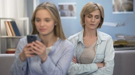 disobedient : Daughter with smartphone in hands ignoring her mom, indifference, puberty age