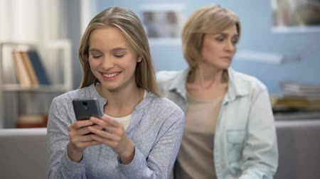 disobedient : Happy teenage girl texting messages in smartphone, sad mother sitting on sofa