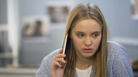 отменить : Student girl looking upset after phone talk with friend, date cancel, bad news
