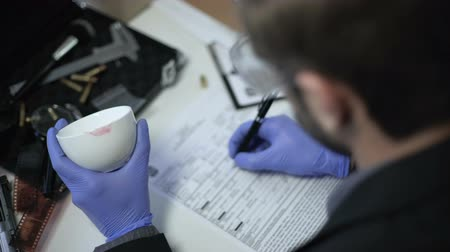 criminalist : Lipstick on cup as evidence from crime scene, officer writing police report