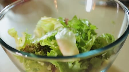 participante : Cooking show participant pouring out healthy organic lettuce in salad bowl