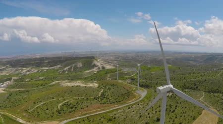 風車 : Flyover above green fields with wind turbines, alternative energy, aerial 動画素材
