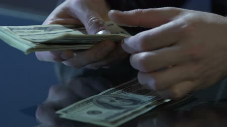 financiamento : Businessman hands counting dollar bills on table, illegal deals, financial crime Vídeos
