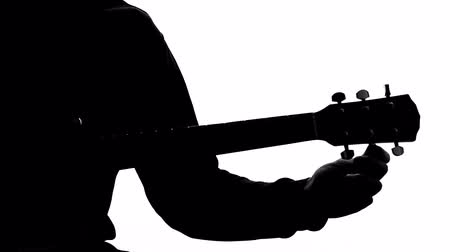 skladatel : Silhouette of male musician tuning up acoustic guitar, young composer.