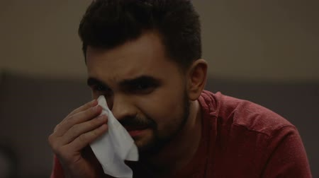 novela : Vulnerable and gentle man wiping tears in his eyes. Vídeos