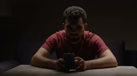 spojrzenie : Depressed man sitting in dark empty room with smartphone, waiting for call