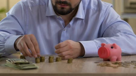 agglegény : Scrupulous bachelor planning his monthly budget, putting coin in piggy bank Stock mozgókép