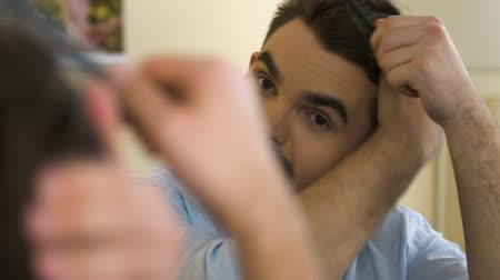 férfiasság : Smiling man combing his hair looking at reflection in mirror, going on date Stock mozgókép