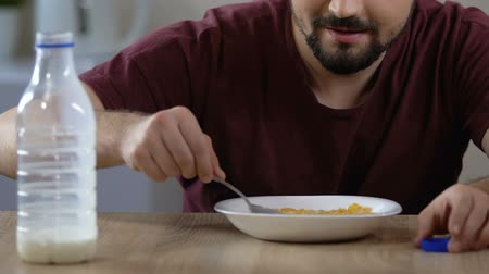 cálcio : Male pouring milk and eating cereal breakfast with pleasure, healthy nutrition