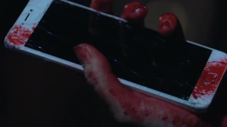 serial : Woman holds broken smartphone in blood, victim of maniac tries to call police Stock Footage