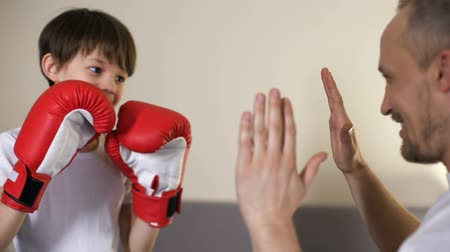 confronto : Cute kid practicing boxing punches with his coach, having fun with father, sport Stock Footage