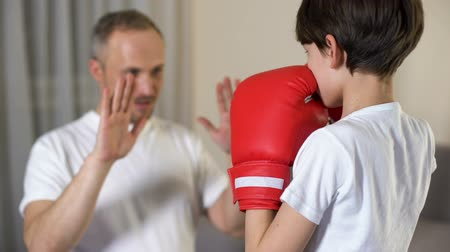 confronto : Little boy boxing with his step-father, learning attacking, family togetherness