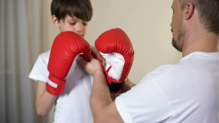 otcovství : Caring father putting on son arms boxing gloves and teaching to defend himself Dostupné videozáznamy