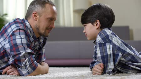 two forces : Dad and his son looking at each other and competing in force, playing game