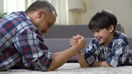 two forces : Little male kid challenging his father in arm wrestling, having fun together