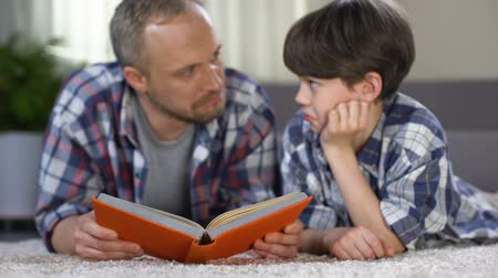 instill : School boy listening to dad reading exciting adventure book, love to literature