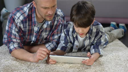 easily : Boy using interactive application on tablet with help of father, family time