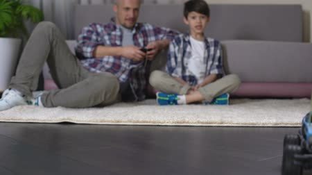 telefonkagyló : Father showing his son how to ride toy car with remote control, birthday gift
