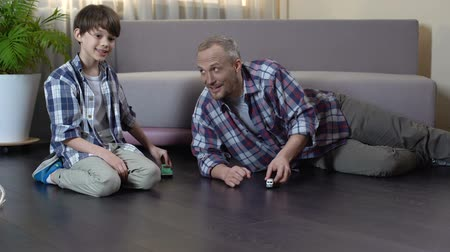 zondag : Dad and his son playing with toy cars on the floor, pleasant time together Stockvideo
