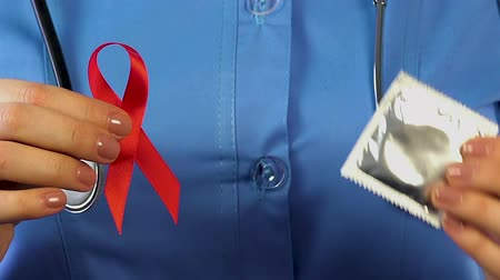 antykoncepcja : Female doctor holding red ribbon and condom in her hands, HIVAIDS prevention