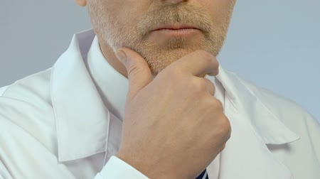 resolver : Middle aged doctor solving problem and making decision with hand on his chin