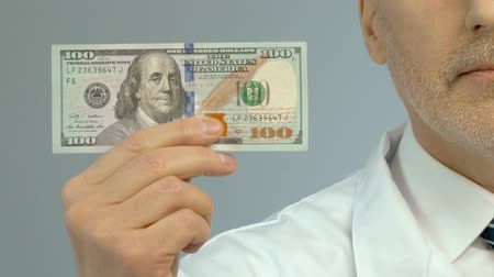 ücretli : Male doctor holding banknote dollar, expensive medication, health insurance Stok Video