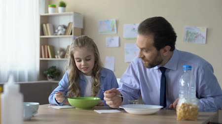 flocos de milho : Happy little girl and father eating cornflakes at breakfast, family traditions Stock Footage