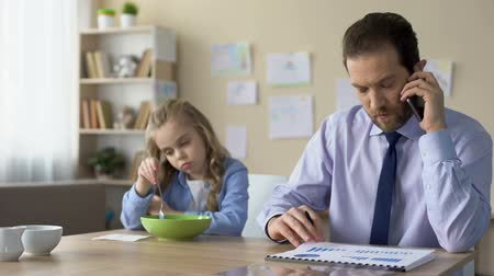 descuidado : Daughter sitting at morning table with busy father, lack of parental attention