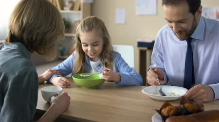 caring : Friendly family eating breakfast and talking, morning ritual, togetherness Stock Footage