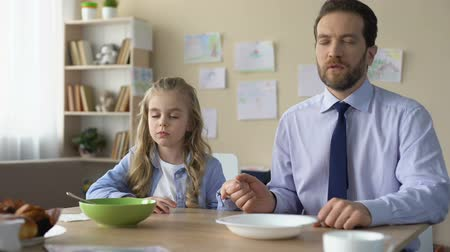 flocos de milho : Pretty girl and her father praying before eating breakfast, spiritual education Stock Footage