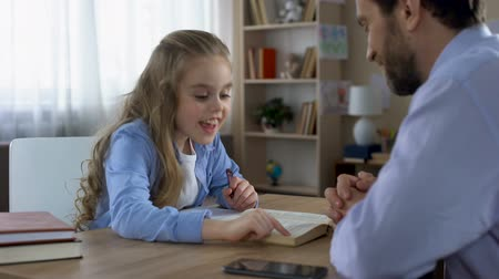 заботливый : Caring dad helping his smiling daughter to do homework, paternal support Стоковые видеозаписи