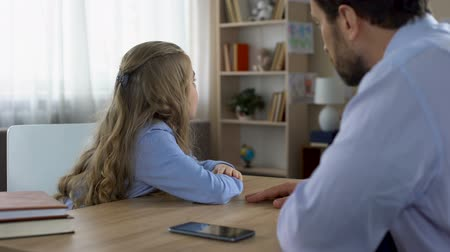 curly haired : Father discussing gadget addiction with his little daughter, generation conflict Stock Footage