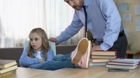 плохо : Badly behaved daughter sitting at table, ignoring fathers remarks, conflict