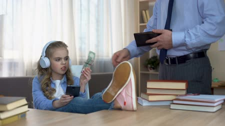 alfabetização : Busy father giving pocket money to little capricious daughter with headphones