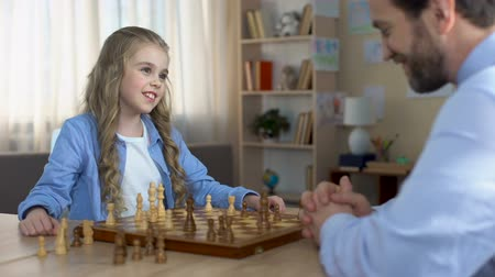 turbina eólica : Little blond girl playing chess with her father at home, hobby and relaxation Stock Footage