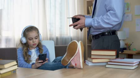 budgettering : Father in suit giving pocket money to daughter listening to music in headphones Stockvideo