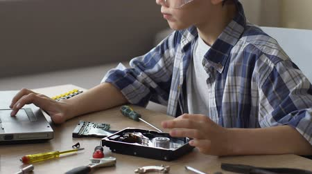 parçalar : Schoolboy searching in internet how to repair HDD, young talent.