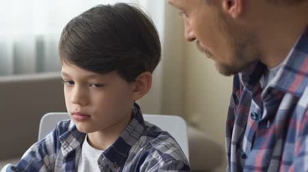 disobedient : Father lecturing son, forcing to do homework, boy looking guilty at dad, closeup Stock Footage