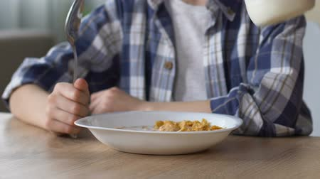 keyifli : Cornflakes with milk for healthy breakfast, boy eating before school, close up