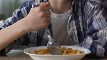 lack : Boy reluctantly mixing cornflakes with spoon, upset child, loss of appetite Stock Footage