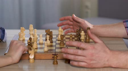 tabuleiro de xadrez : Smart child wins chess, handshaking with his proud father, chessboard close up
