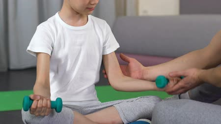 родственники : Boy sitting and lifting dumbbells with trainer support, father help.