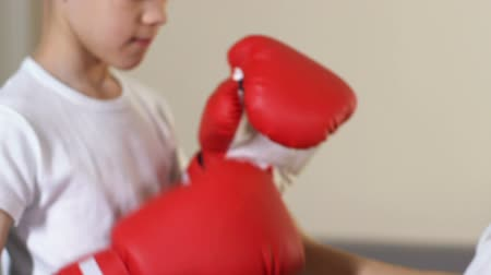 muhalefet : Father helping son to put on boxing gloves, training at home, sport education Stok Video