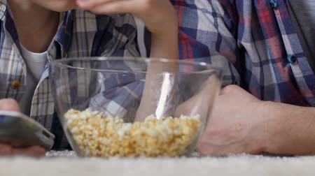 watch tv : Male hands taking popcorn from glass bowl during watching tv, unhealthy food