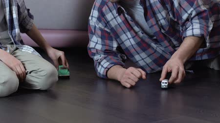zabawka : Father and son playing with toy cars on floor at home, having fun together